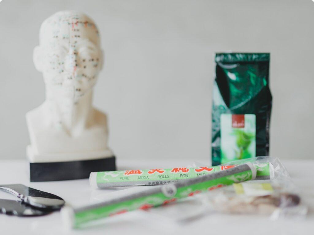 Traditionelle Chinesische Medizin - 2 Moxastangen, eine Packung Tee, eine kleine Packung chinesische Kräuter, 2 Gua Sha Schaber und eine Kopf aus Plastik mit Meridianen darauf eingezeichnet