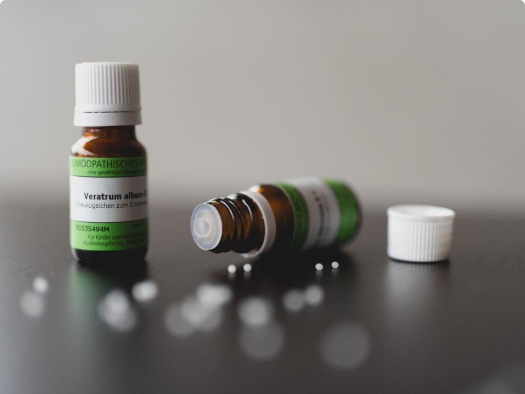 Homöopathie - 2 Fläschchen mit Globuli, eines stehend und eins liegend, einige Globuli sind verstreut am Tisch