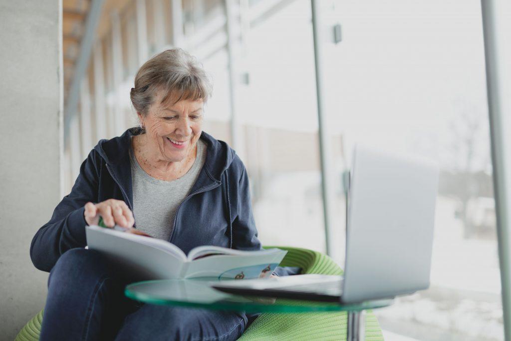 Anonymität für sensible gesundheitliche Anliegen und Fragen - Flotte, ältere Dame schaut sich Ihren Befund MY Healthy Life in Buchform an