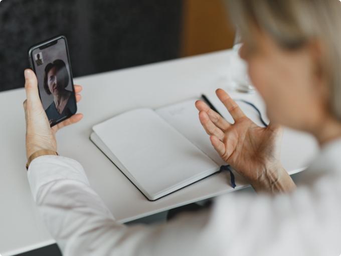 Willkommen in meiner Praxis - Frau führt ein online Gespräch am Mobiltelefon mit Dr. Fröhlich