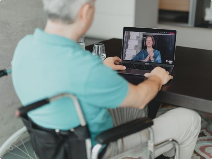 Arzt-Patienten Kommunikation - Mann mit grünem Shirt sitzt im Rollstuhl sieht auf einen Laptop vor sich, man sieht Dr. Fröhlich am Laptop Bildschirm. Die beiden sind in einer Videokonferenz.